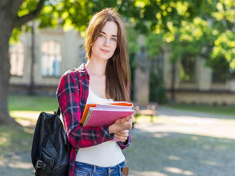 Retrato de colegiada con libros en el parque